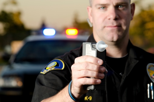 A police officer holds up a breath test device