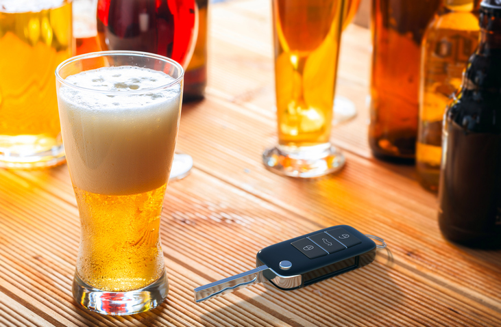 Car key and beer glass on a wooden pub counter.